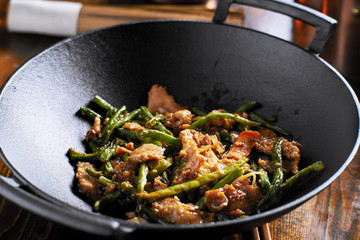 large cast iron wok with chicken and stringbean stirfry