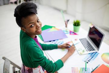 Creative fashion designer sitting by workplace