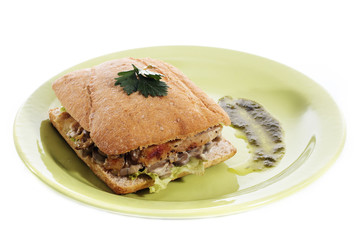 Healthy chicken and mushroom sandwich on green plate over white background