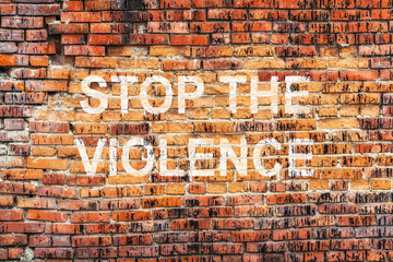 Text STOP VIOLENCE on stained old orange brick wall texture background