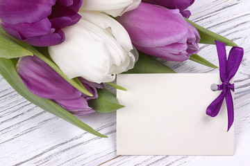 Purple and white tulips with white paper on a white wooden background with card for text. Womans Day. 8 March. Mother's Day.