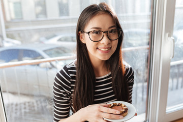 Smiling Asian woman on windowsill with cake