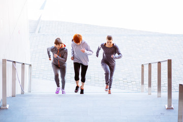 Front view of the group of three athletic women running up stairs during cardio - interval training.