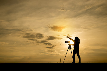 Silhouette of a photographer,he use a tripod.The background image is a sunset in Thailand.