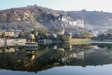 Misty morning at Nawal Sagar Lake with reflections of Bundi Palace and mountains, bundi, Rajasthan, India