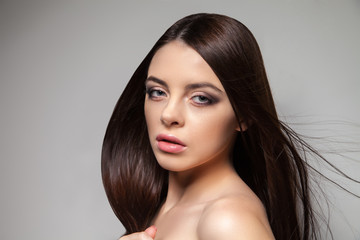 Young pretty brunette woman looking at camera. Horizontal studio shot.