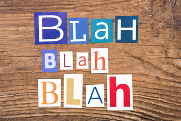 "Phrase ""Blah, blah, blah"" in cut out magazine letters on wooden background"