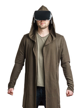 Isolated portrait of an young man in a hoodie wearing vr glasses and clenching his fist.
