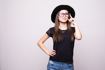 Young girl doing emotion. Dressed in a black shirt, black hat, glasses in studio