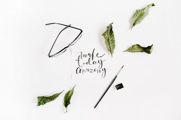 "Inspirational quote ""Make Today Amazing"" written in calligraphic style on paper with green leaf and glasses on white background. Flat lay, top view"