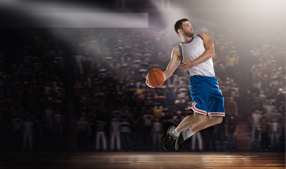 basketball player jumping with ball on stadium in lights