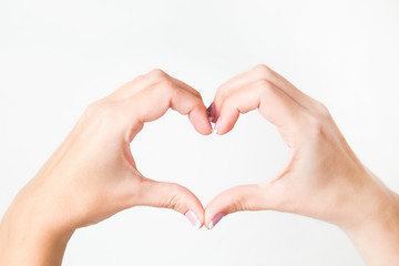 Close up of two female caucasian hands isolated on white background. Young woman forming shape of heart with her fingers. Horizontal color photography. Point of view shot.