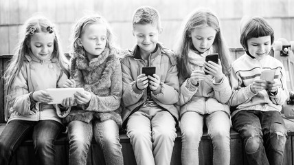 girls and boy with smartphones on bench in park