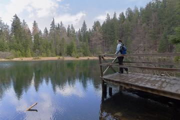 Girl tourist with a backpack on the shore of a forest lake. Travel