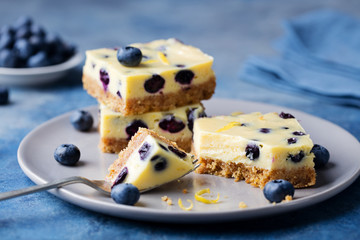 Blueberry bars, cake, cheesecake on a grey plate on blue stone background