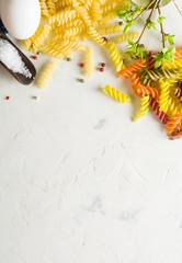 spiral pasta on a white stone background.