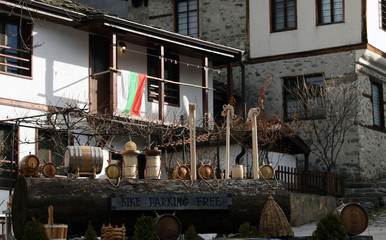 Handmade household tools and utensils made of wood against the houses of the Rhodope village of Shiroka Laka, Bulgaria