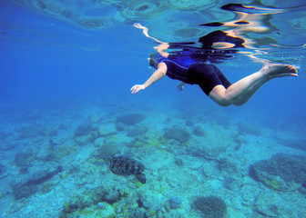 Woman swimming with sea turtle. Tropical sea background.