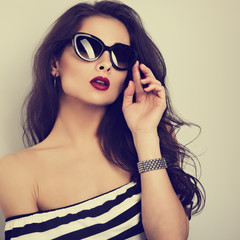 Chic female model with long hair posing in fashion sunglasses in striped dress with hand near face. Toned color closeup portrait