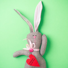 Easter bunny on a green background. Rabbit. Easter ideas. Easter eggs. Space for text. Black lettering on a heart happy easter.