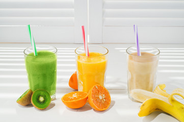 Freshly blended fruit smoothies in glasses on a white wooden background. Fresh fruit cocktails of various colors and tastes, kiwi, banana, orange. Assorted fruit shakes. Diet concept.