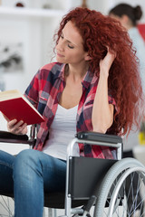 disabilty and handicap young disabled woman on wheelchair reads book