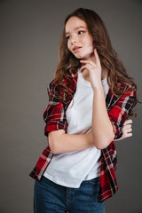 Pensive young woman in plaid shirt thinking and looking away