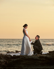 Groom stand on knee and hold bride hand