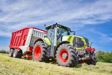 Landwirtschaft - Ernte, Traktor mit Ladewagen bei der Grasernte