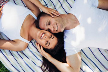 Beautiful horizontal and top view of a attractive couple in love lying on a picnic blanket holding face with hand. Happy caucasian man and brunette woman with healthy teeth on  plaid in tropical.