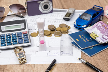 time to travel - passport, money, camera, watch, calculator, glasses, calendar toy car on wooden table.