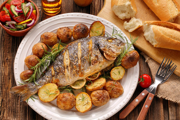 Fototapeten Fisch Grilled fish with baguette and vegetables on the plate