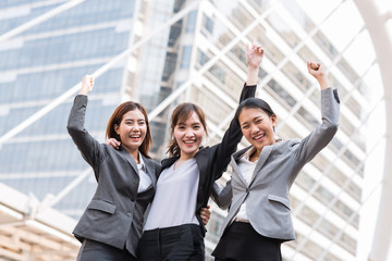 Happy young Asian businesswoman team arm up to celebrate their success outdoor in city