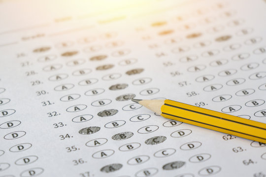 A pencil sitting on a test bubble sheet, optical form of an examination,Answer sheet with pencil,Standardized test form with answers bubbled and a black pencil,selective focus,vintage color