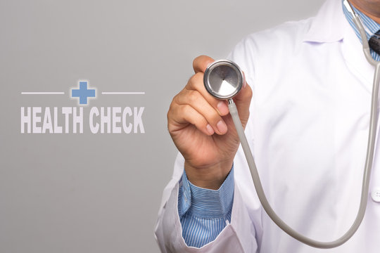 """Doctor holding a stethoscope and word """"HEALTH CHECK"""" on gray background. concept Healthy."""