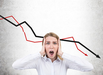 Stressed businesswoman and falling graphs