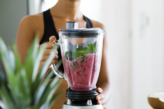Woman blending spinach, berries, bananas and almond milk to make a healthy green smoothie