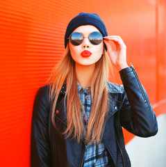Fashion portrait beautiful blonde woman sends air kiss blowing red lips outdoors wearing sunglasses and hat