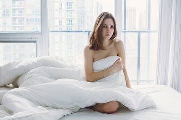 Portrait of young pensive Caucasian woman sitting in bed after waking up, indoors at home early morning, lifestyle, toned with filters