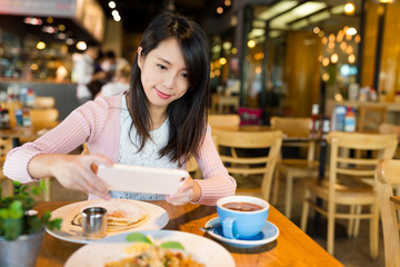 Woman taking photo on her dish before eating