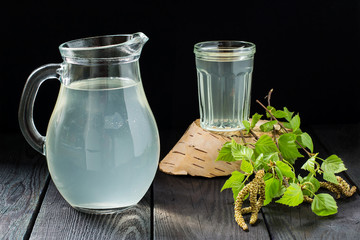 Fresh birch juice in a jug and glass and birch branches