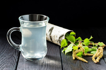 Fresh birch juice in a glass and birch branches