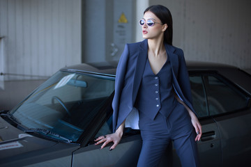 Mafia lady outside japonese car in the sea port. Fashion girl standing next to a retro sport car on the sun. Stylish woman in a blue suit and sunglasses waiting near classic car.