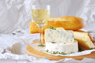 Cheese plate with different kinds of cheese with white wine