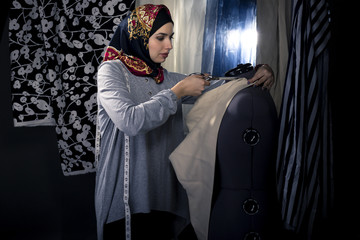 Female fashion designer tailoring conservative clothing in a textile workshop.  The hijab she is wearing is associated with muslims, middle east or eastern european cultures.