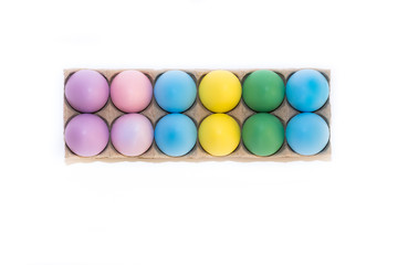 A dozen colored Easter eggs dyed lavender, pink, blue, yellow and green in a cardboard cartoon from above on a white background with copy space.