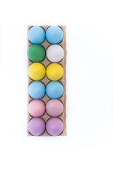 Eleven Easter eggs dyed lavender, pink, blue, yellow and green with one undyed white hen's egg in a cardboard carton from above on a white background with copy space.