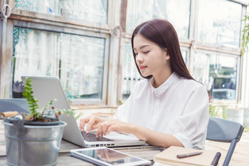 young casual asian woman using technology on her laptop computer outdoor in her garden