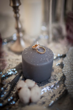 Wedding rings on a candle. Decorations sprinkled with snow.