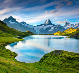 Wetterhorn and Wellhorn peaks reflected in water surface of Bachsee lake